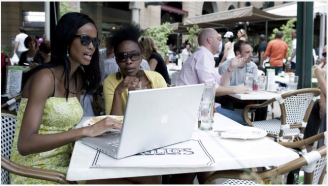 women working at laptop - outdoor cafe