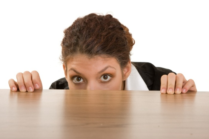 nervous woman hiding behind table